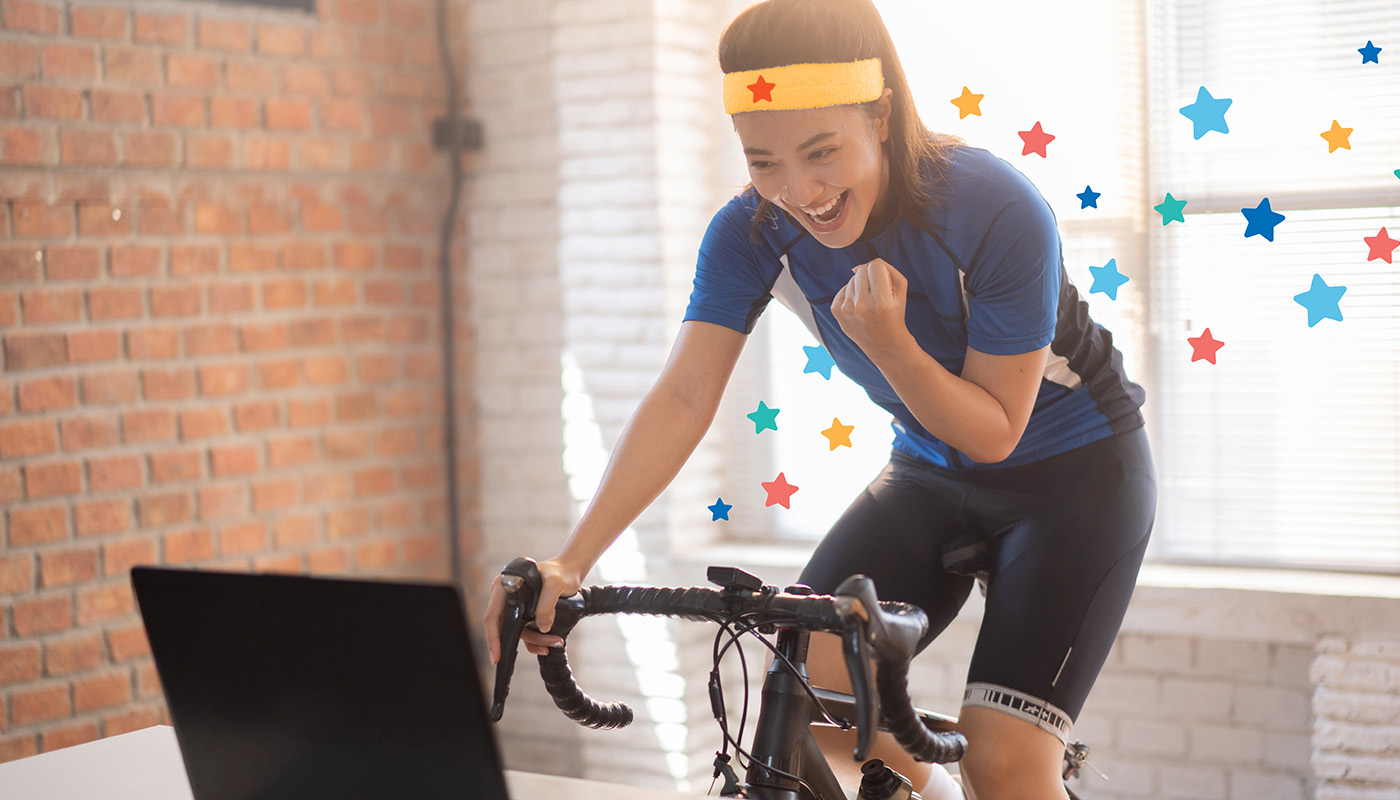 Woman on exercise bike at home wearing a superhero headband